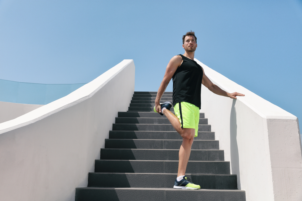 man on stairs doing quad stretch with bent knee