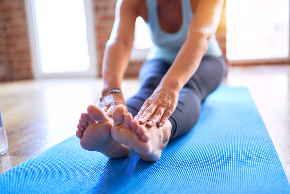 close up of woman doing seated forward fold stretch