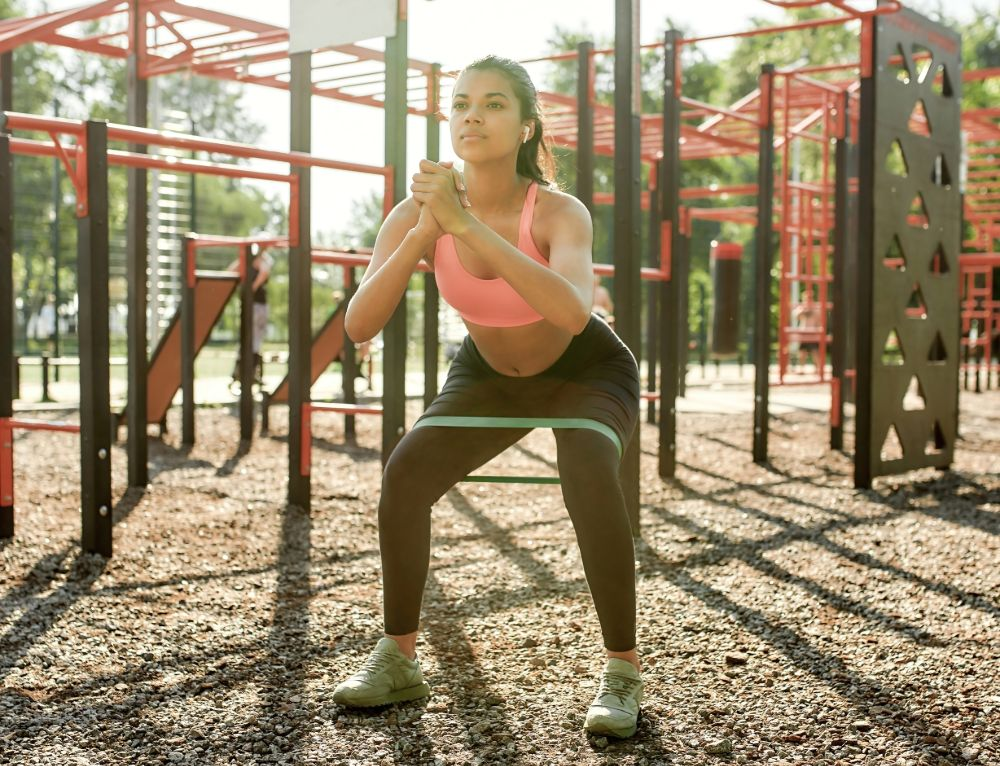 woman working out in playground with resistance band