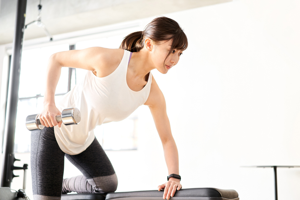 woman at gym doing one arm row exercise