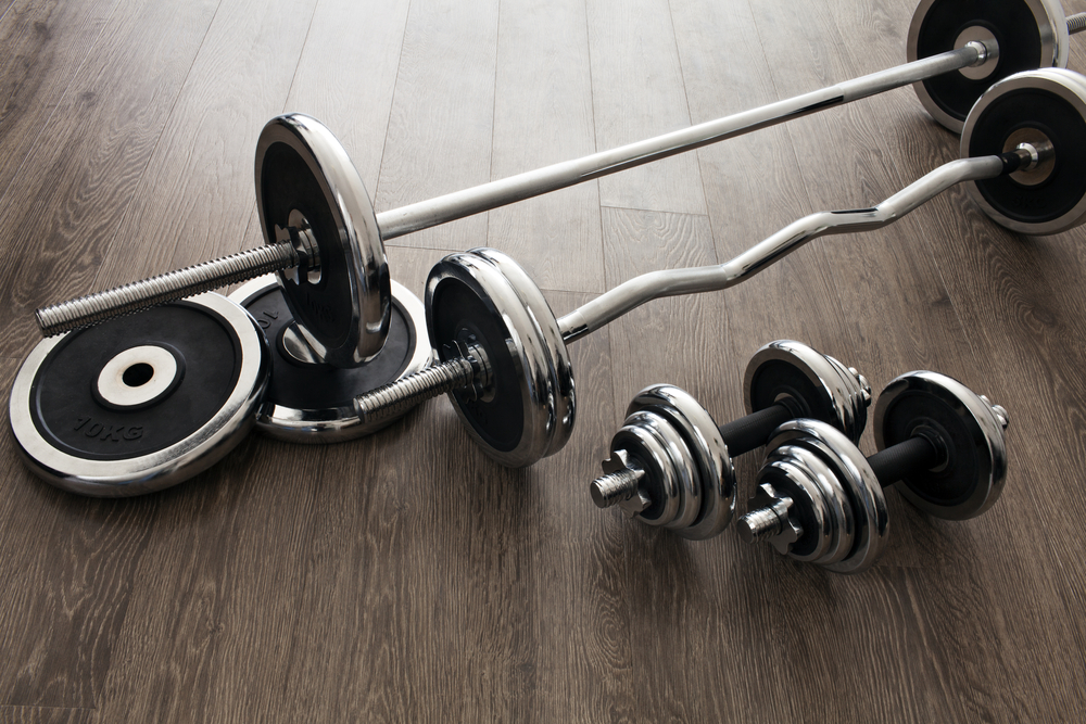 barbells and dumbbells side by side on floor