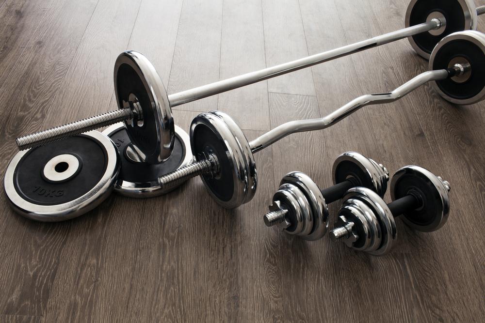 barbells and dumbbells side by side on floor