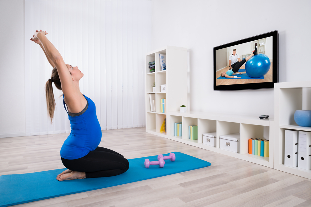 pregnant woman following a workout routine on her tv