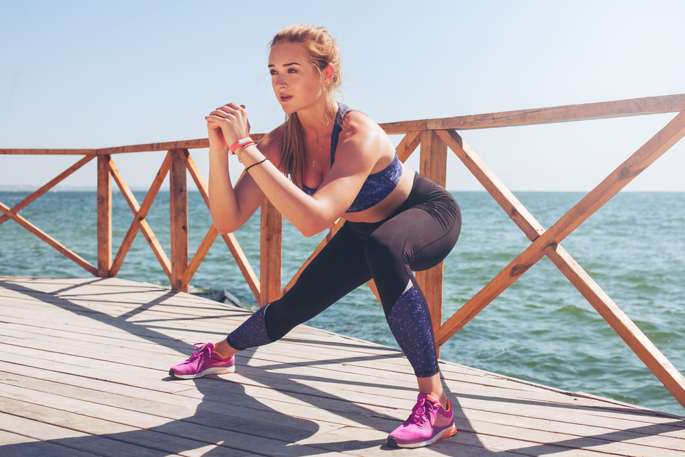 woman by water doing lateral lunge stretch