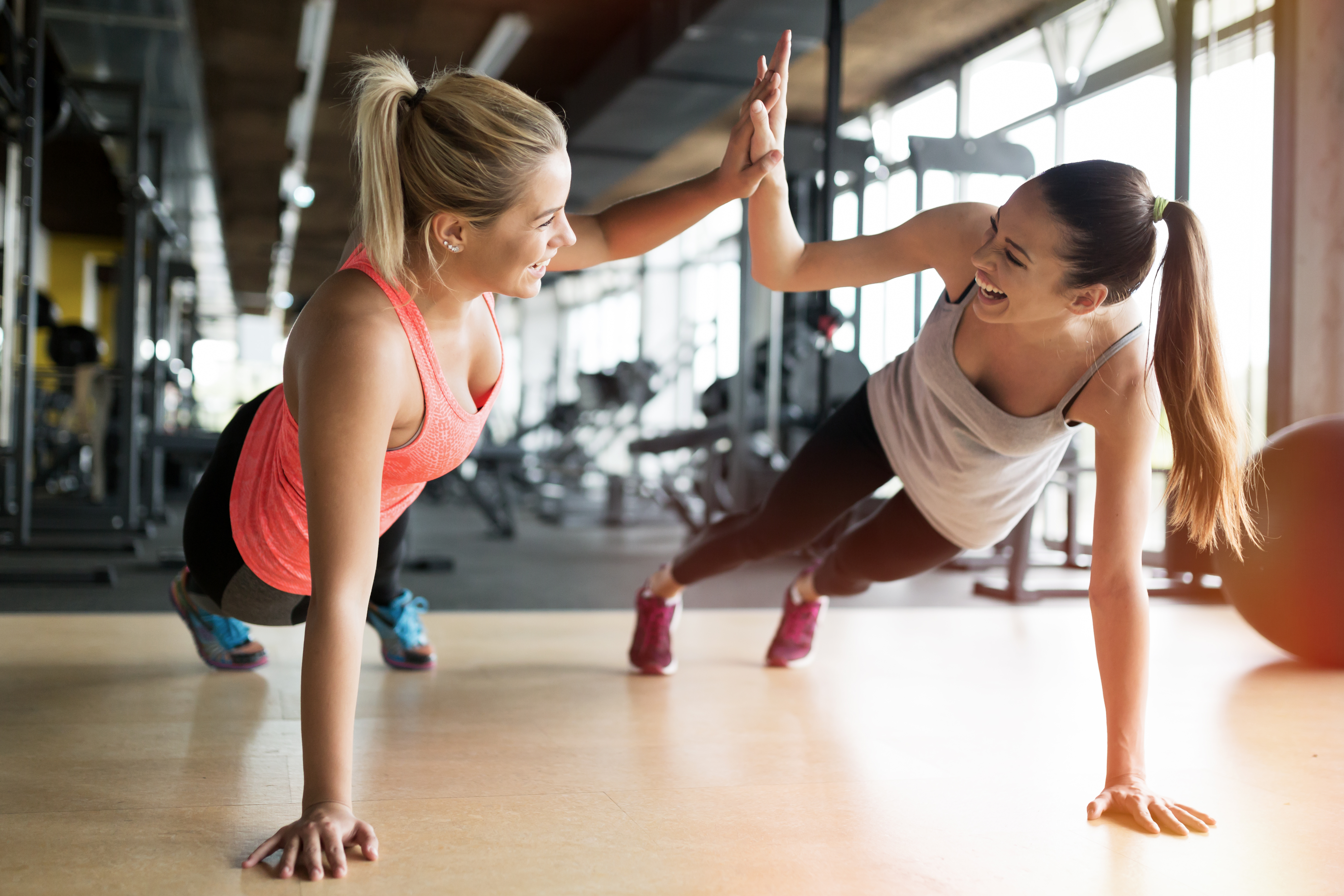 two women working out and smiling