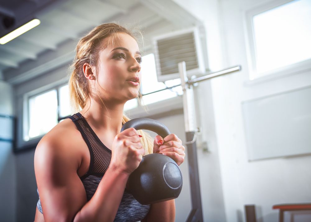 woman in gym holding kettlebell goblet carry