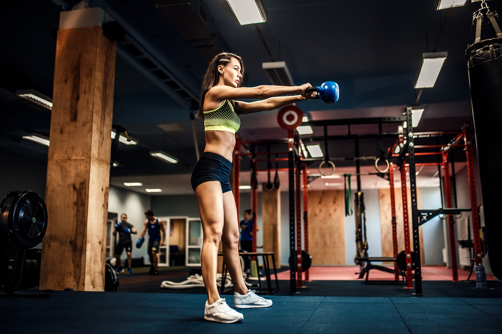 woman in gym performing kettlebell swing exercise