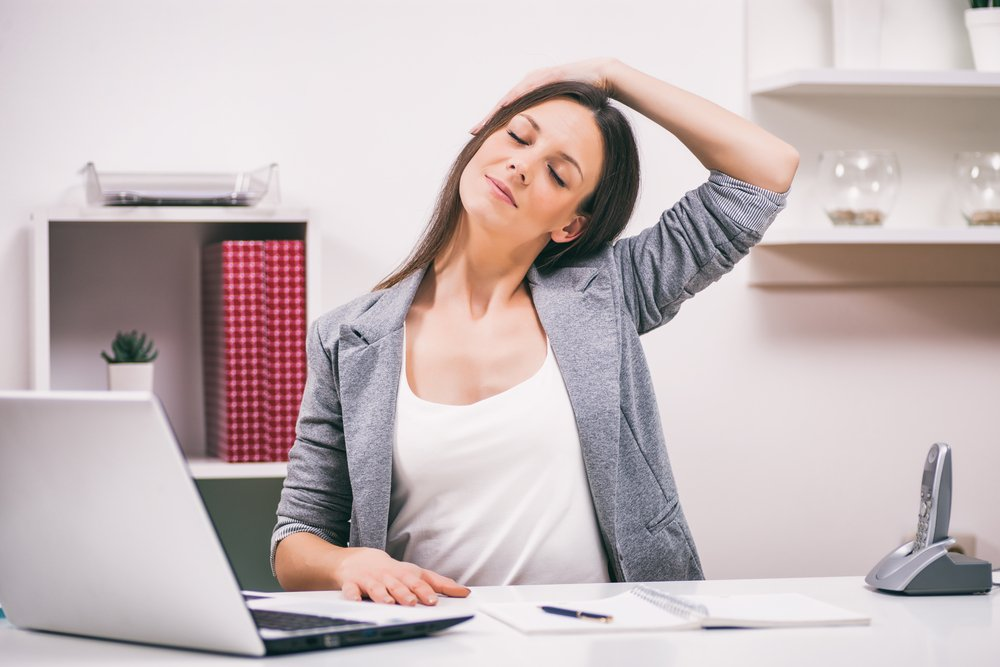 woman at desk stretching her neck