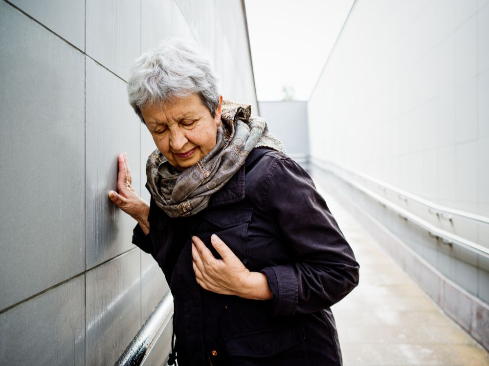 older woman outside holding her chest, in pain