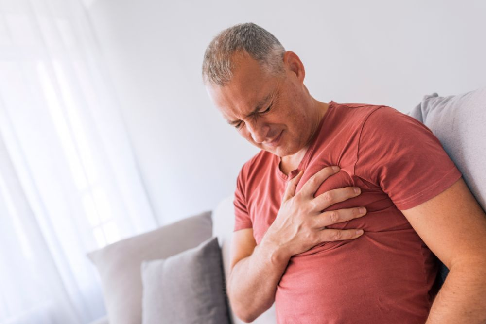 older man on couch clutching chest