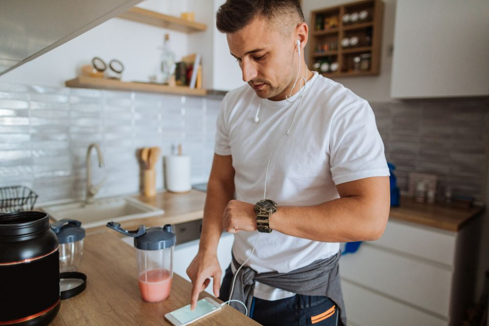 man in kitchen with smoothie checking phone