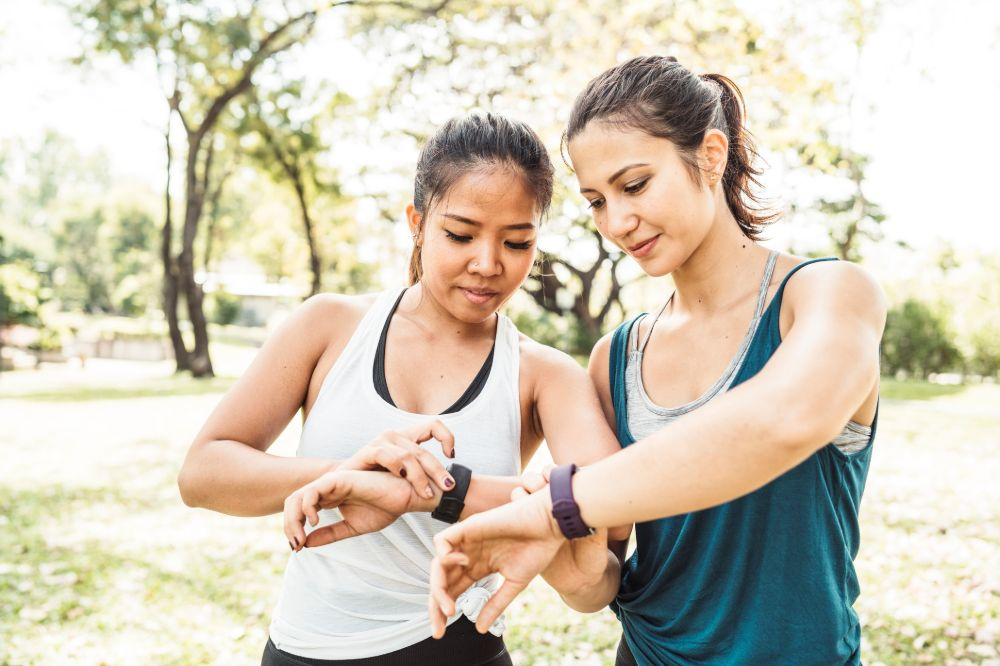 two young women compare jog statistics with tracker