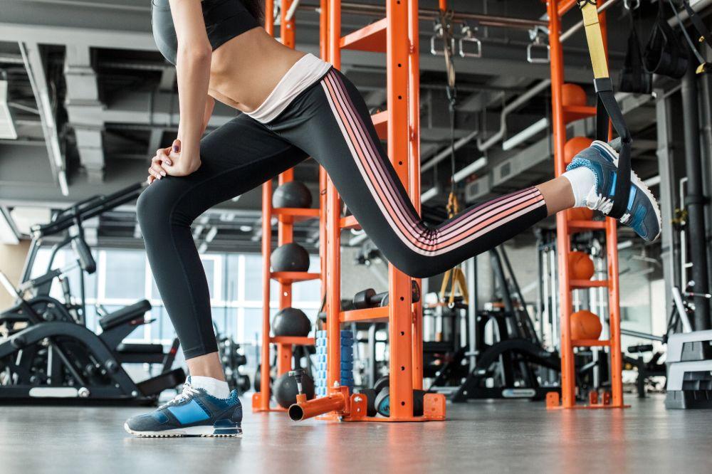 woman at gym doing bulgarian split squat using TRX