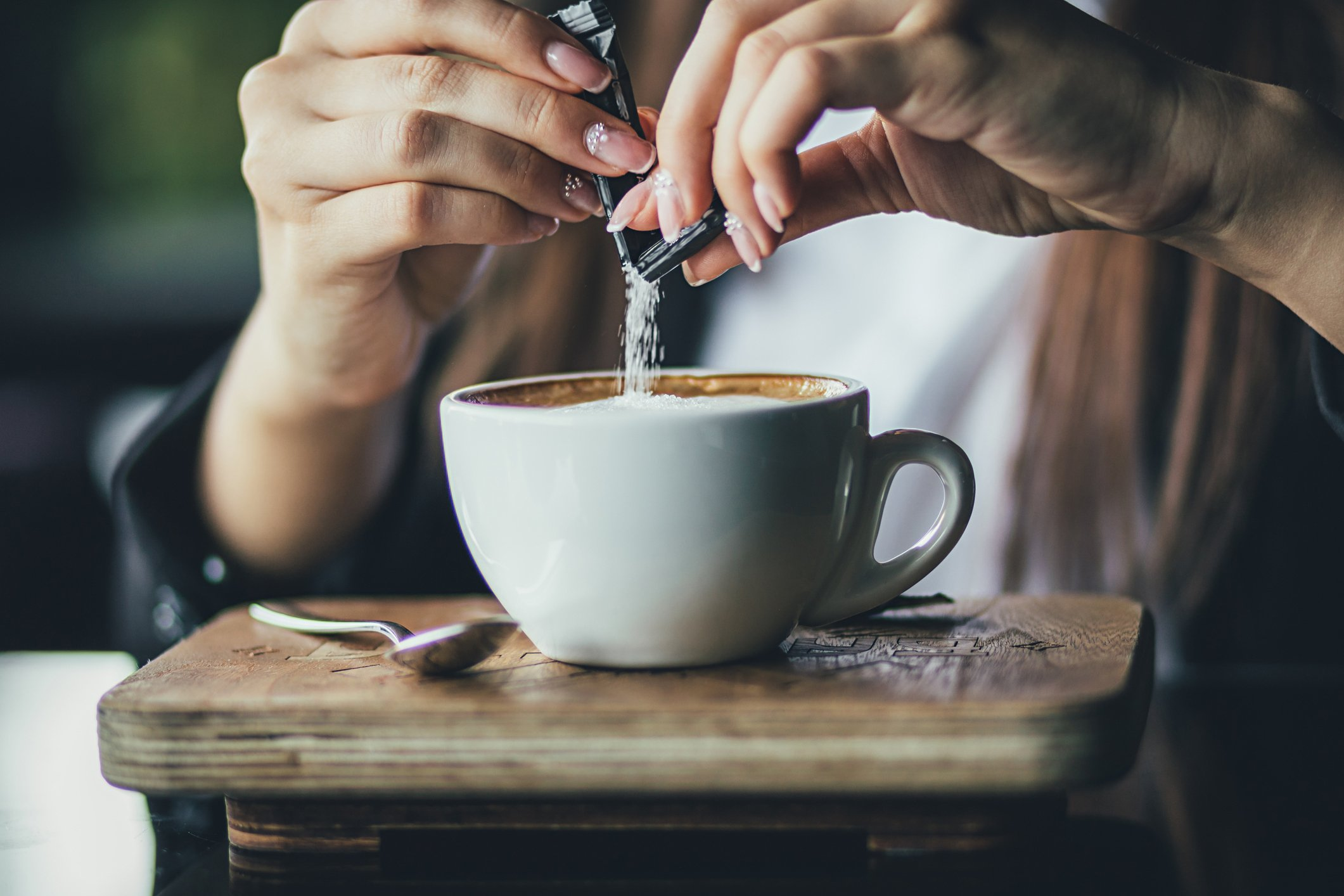 Person pours sugar into their coffee.