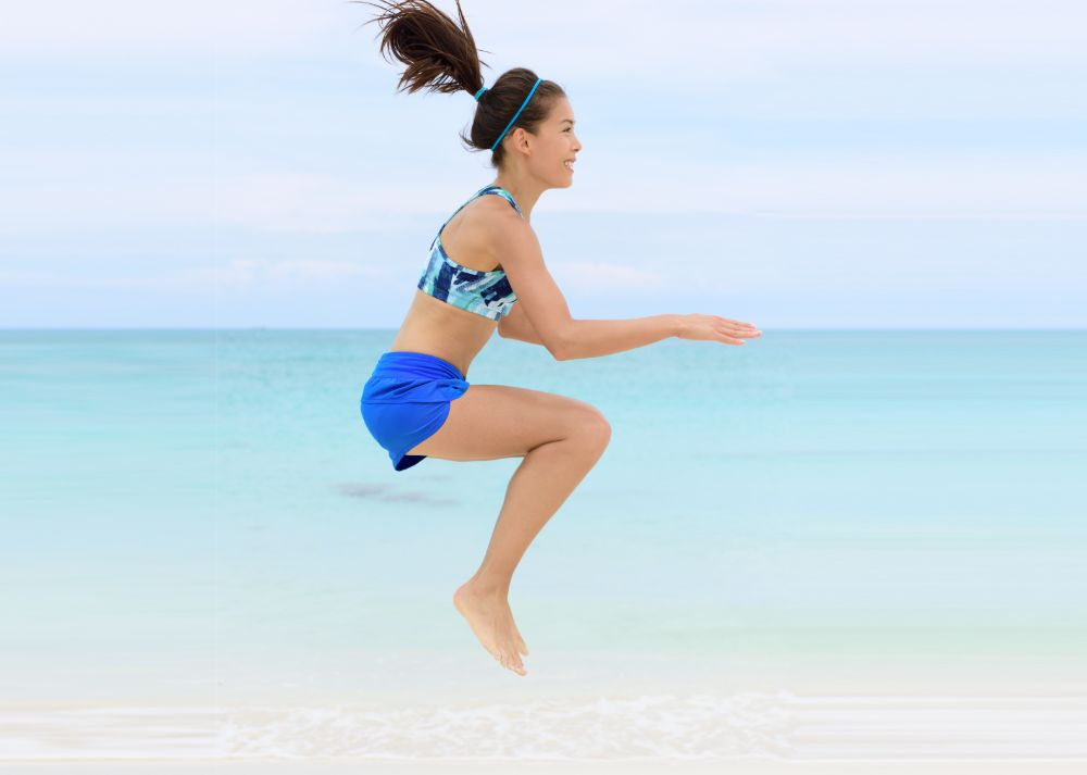 young woman doing jump squats on the beach