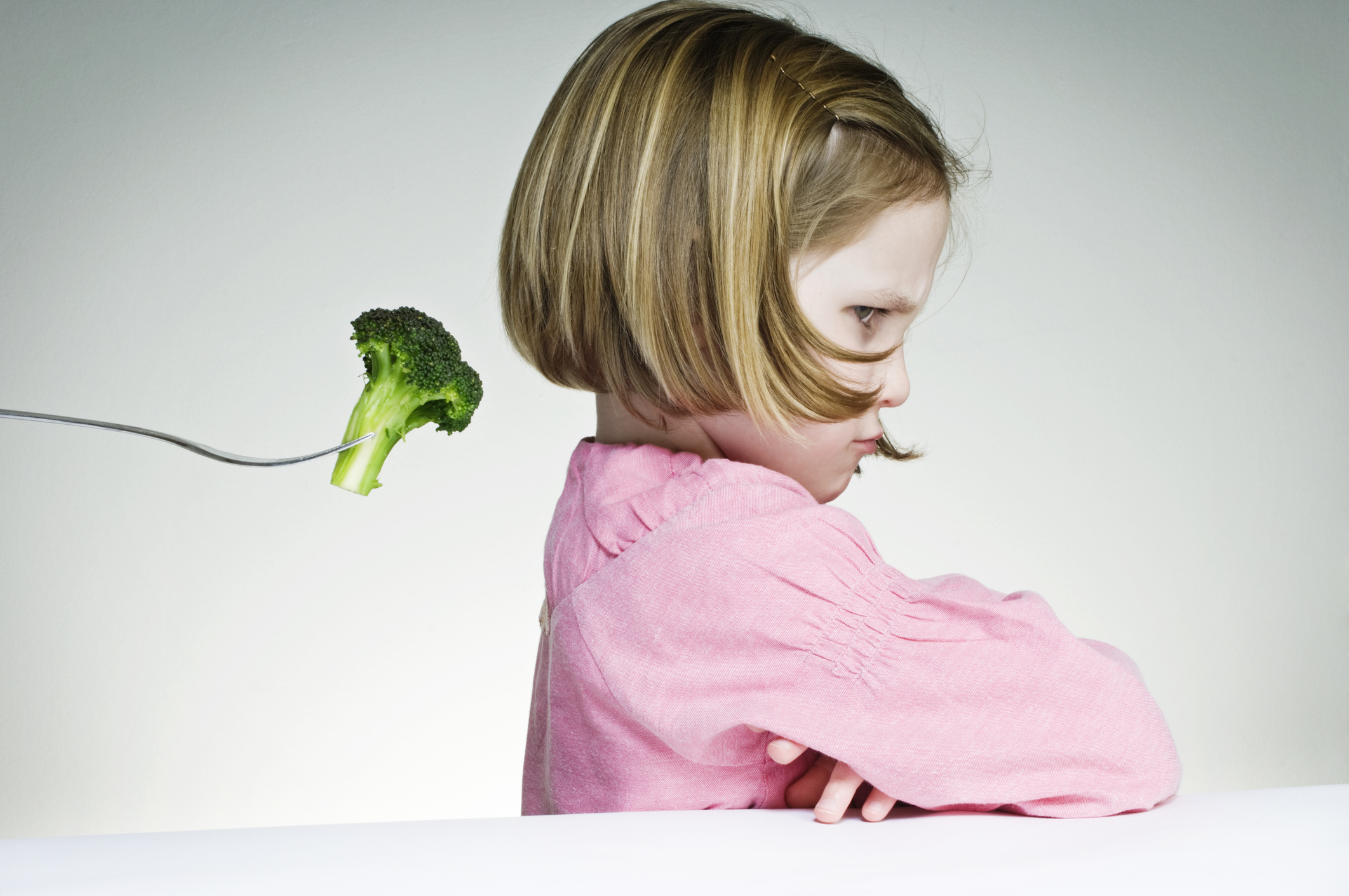 Five year old girl who is not keen on eating her greens.
