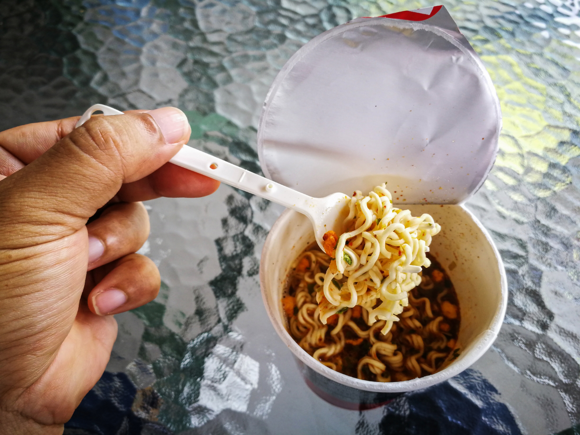 Hot and Spicy Instant cup noodles with shrimp on glass table