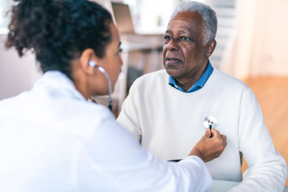 older man and doctor getting heart checked with stethoscope