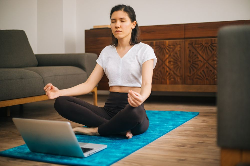 young woman meditating at home with online video