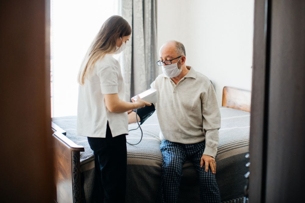 man and nurse in care home, checking blood pressure