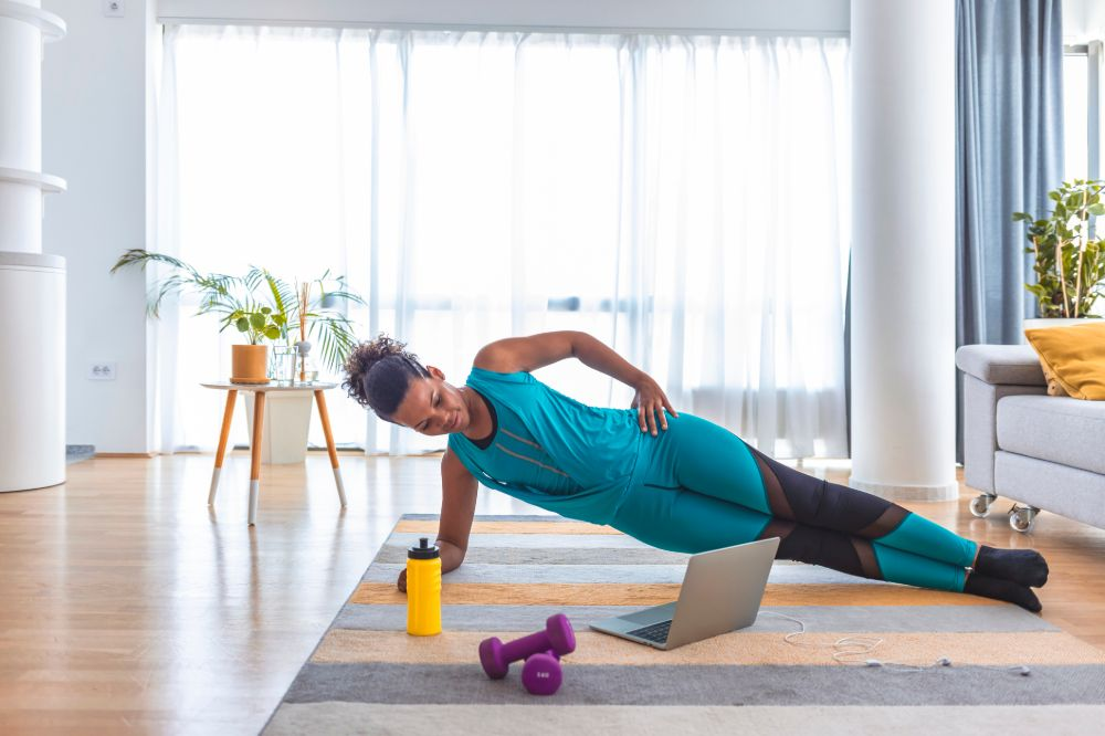 woman doing side plank in living room watching fitness video