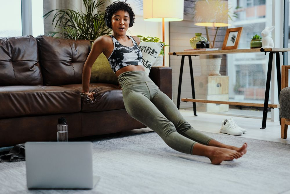 woman working out at home using couch, watching fitness video