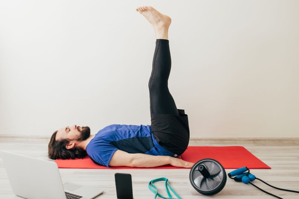 man doing video workout with various fitness equipment