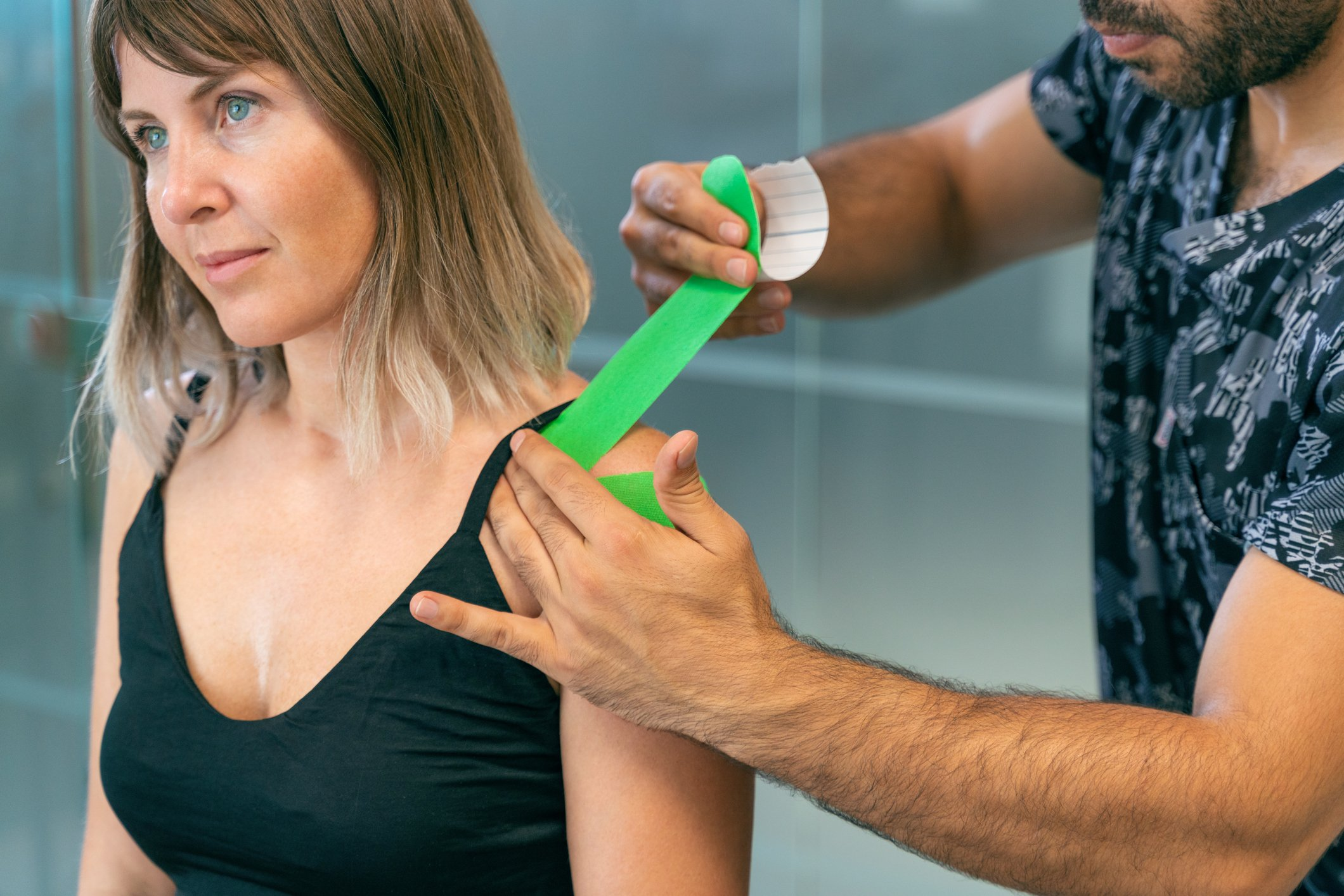 a therapist applying kinesio tape to a woman's shoulder