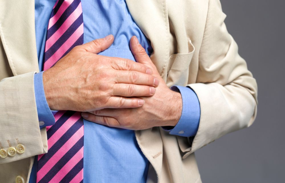 close up of older man in suit clutching chest