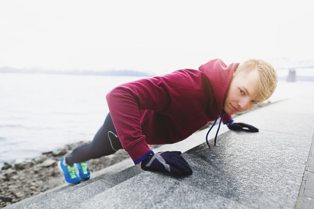 man doing incline pushups on stairs at the beach
