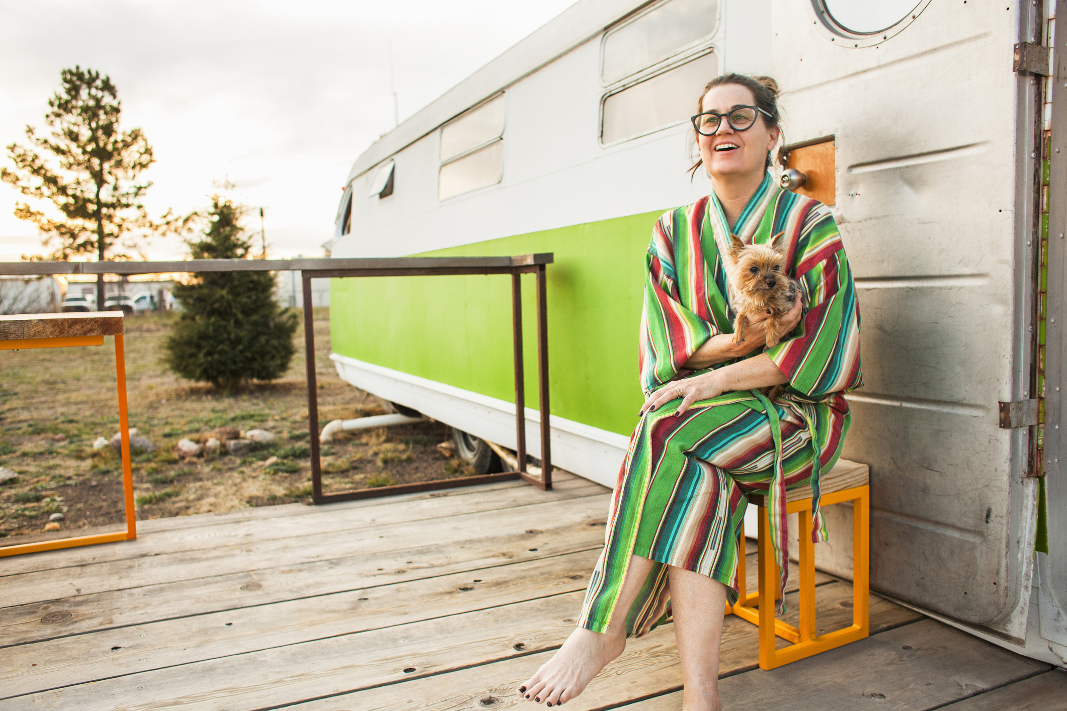 Woman wearing eyeglasses and colorful bathrobe sits outside her vintage tailer while holding her small dog in the morning.