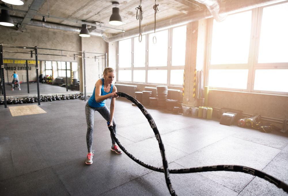 woman in gym using battle ropes