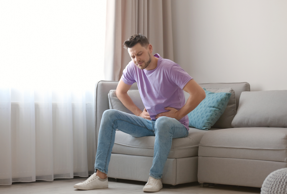young man with stomach pain sitting on couch