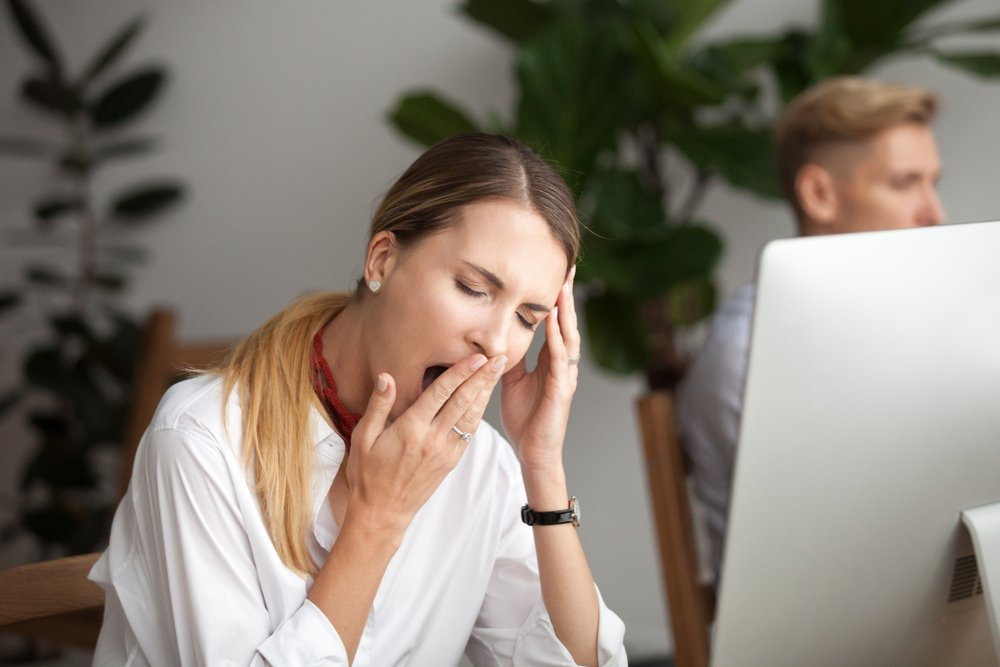 woman at office yawning at her desk