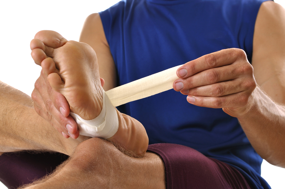 man applying white athletic tape to the arch of his foot
