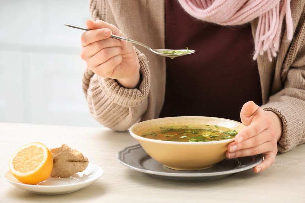 close up of woman eating chicken soup broth