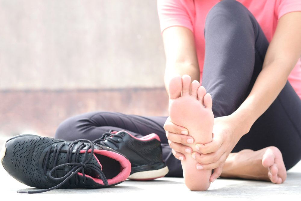woman sitting beside running shoes holding her foot