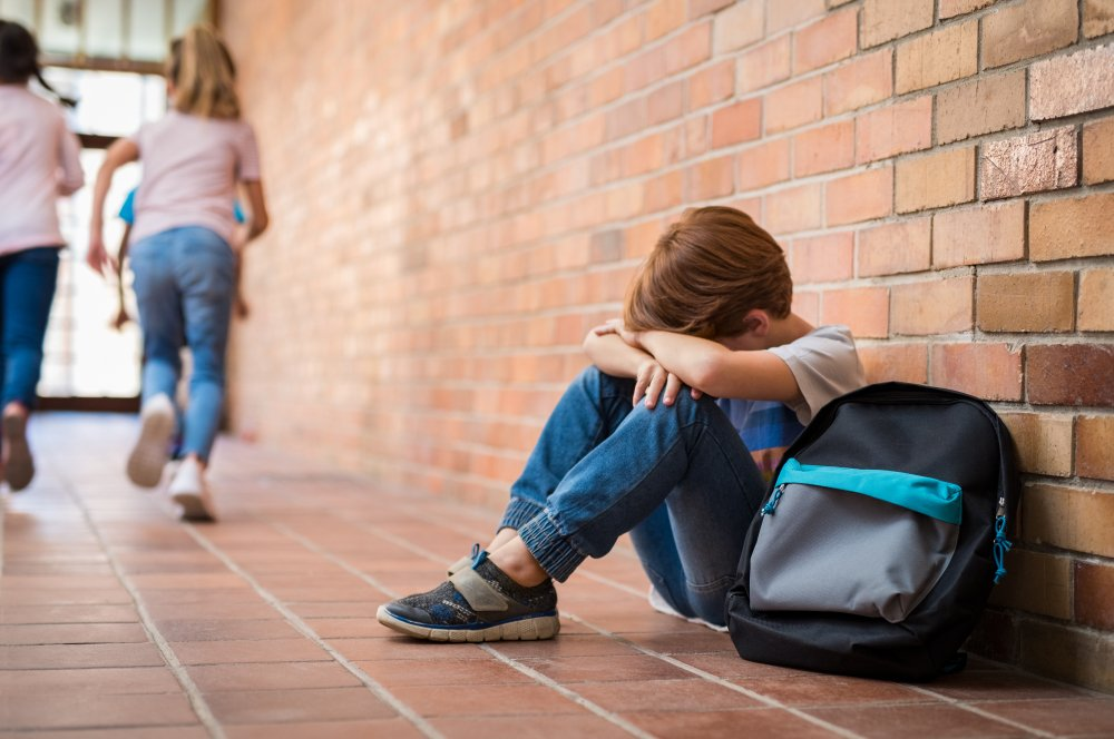 little boy sitting alone at school while children run to play