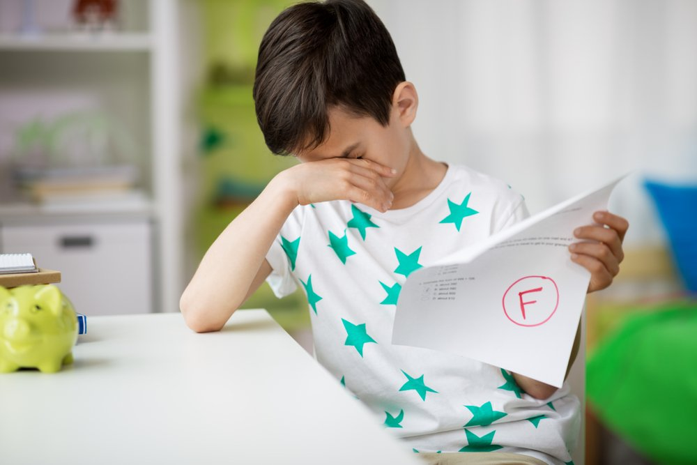 little boy holding test paper with F grade
