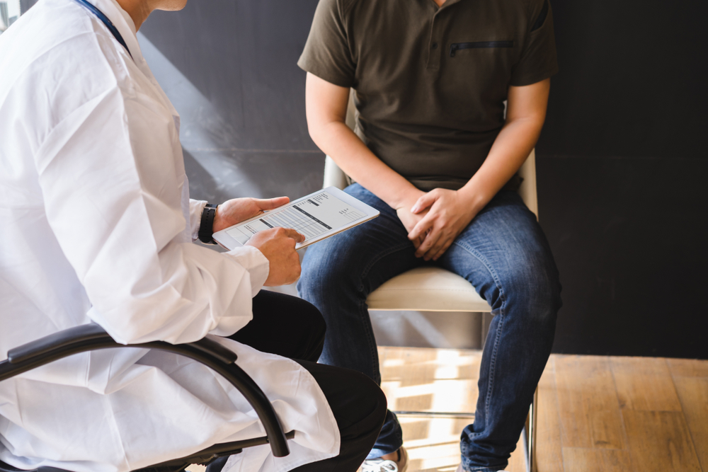 man talking with doctor with a clipboard