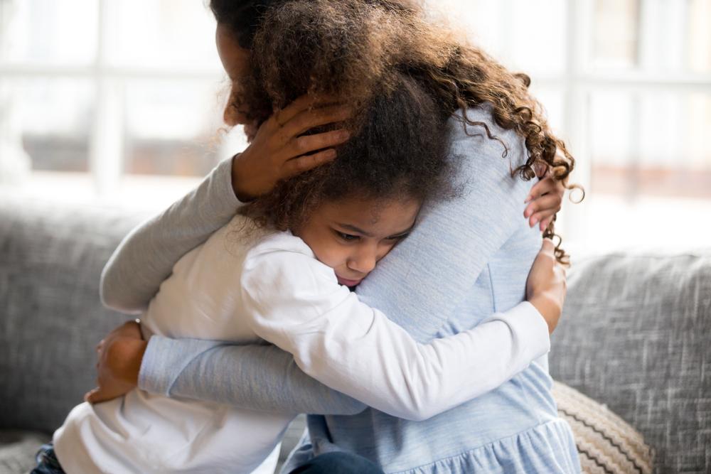sad little girl hugging her mom