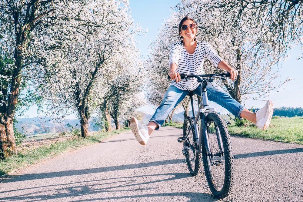 a woman on a bicycle on cherry blossom-flanked lane