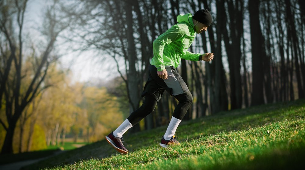 man doing hill sprints up a grassy incline