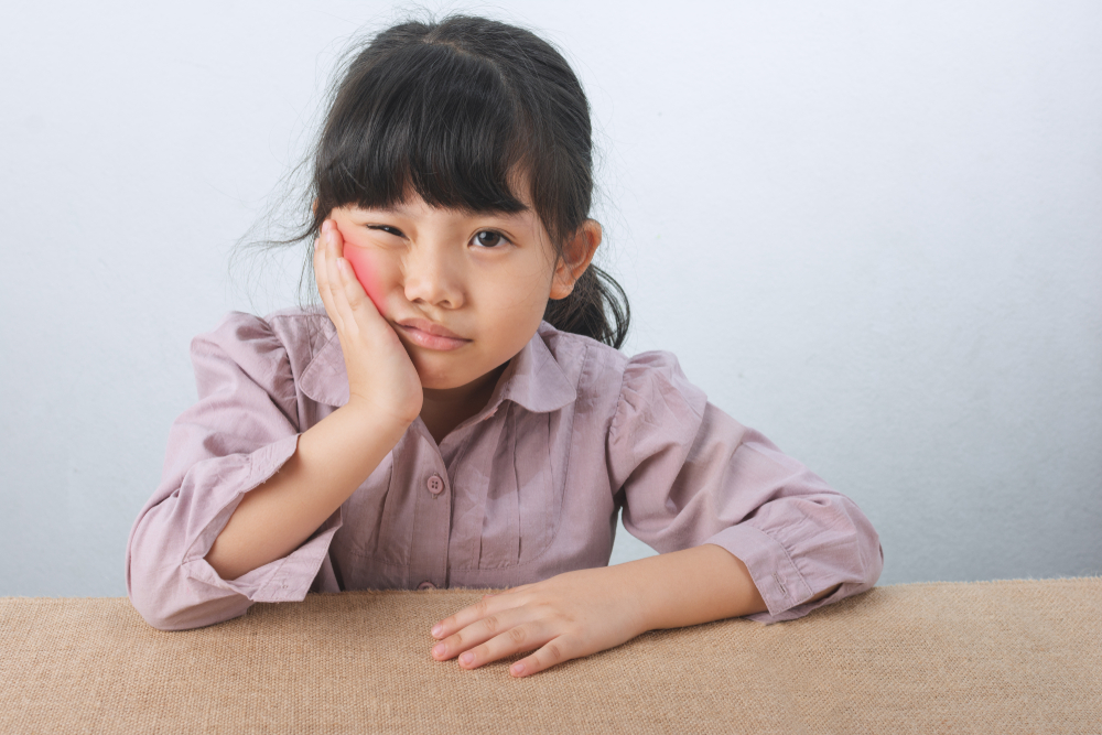 little girl leaning on table holding her sore jaw