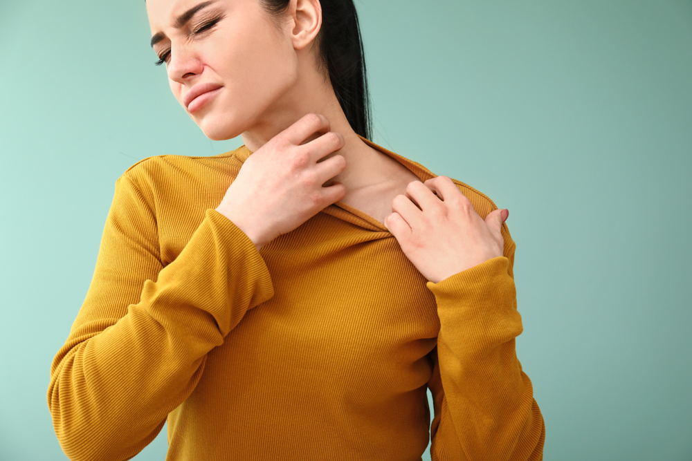 young woman scratching her itchy neck