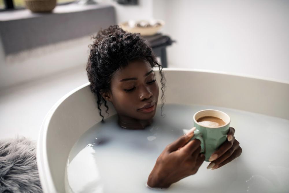 woman having a bath with a warm drink