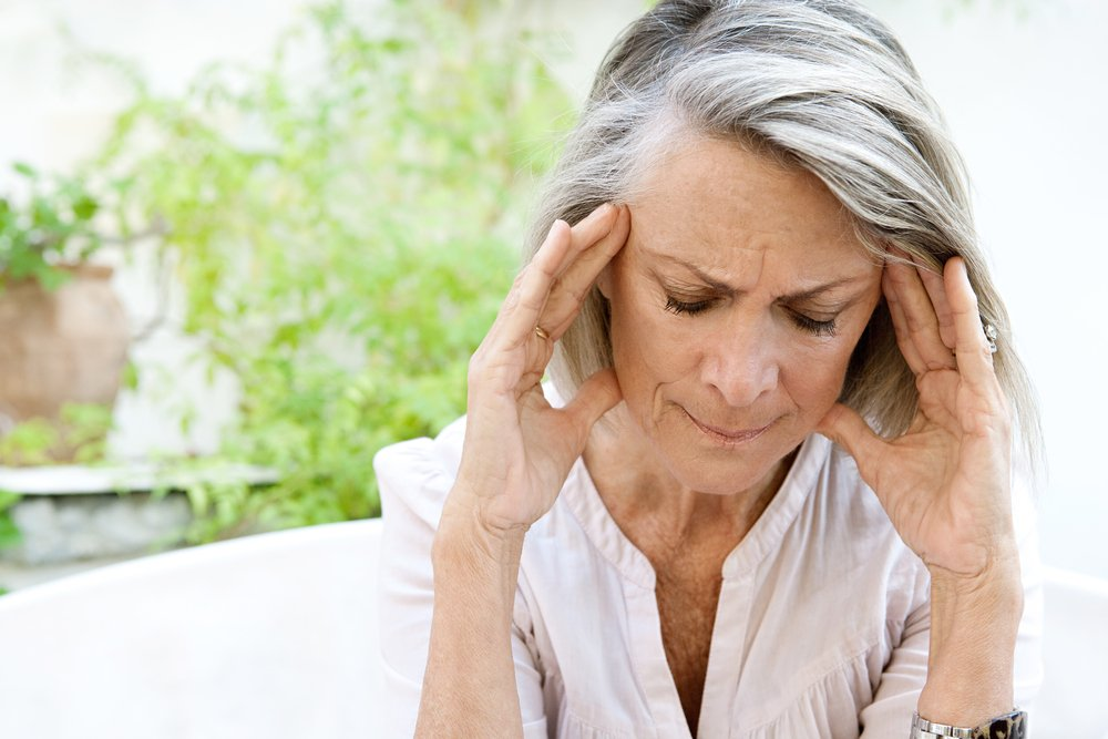 older woman holding her head and looking in pain