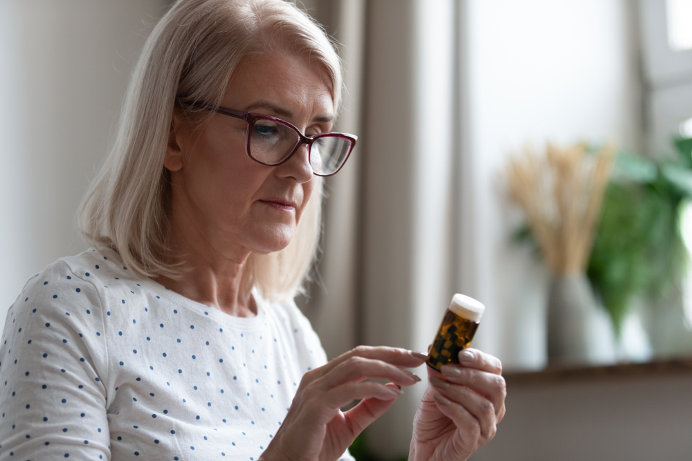 older woman reading instructions on pill bottle