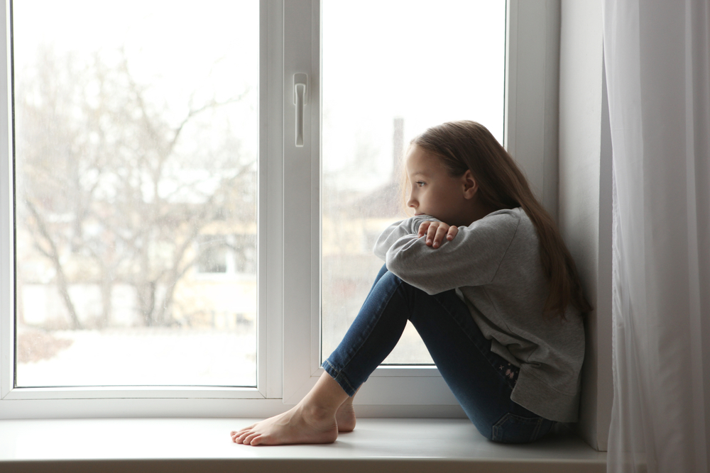 little girl sitting on window ledge looking sad