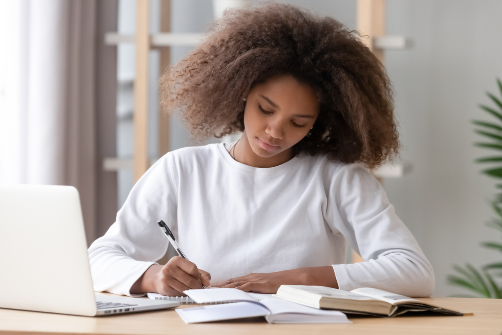 studious young woman with books and laptop open on desk